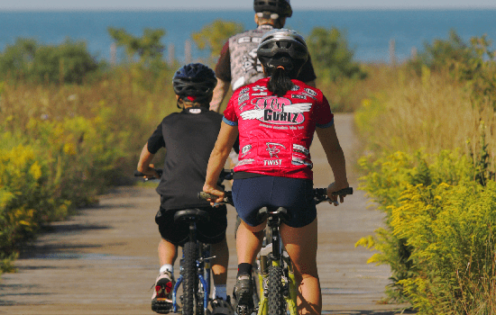 photo of family riding bikes on boardwalk beside cobourg beach