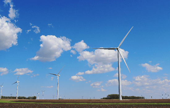 photo of windmills against blue sky with clouds