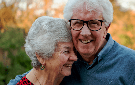 photo of senior couple embracing and smiling